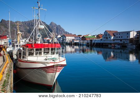 Henningsvaer Norway - August 19 2017: Picturesque fishing port in Henningsvaer on Lofoten islands Norway with typical red wooden buildings and small fishing boats