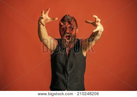 Halloween man devil with zombie hands on orange background. Demon with red blood eyes beard wounds. Satan with bloody horns on head. Aggression evil horror concept. Holiday celebration cosplay. poster