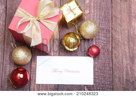 Christmas gift box with red and gold balls .
