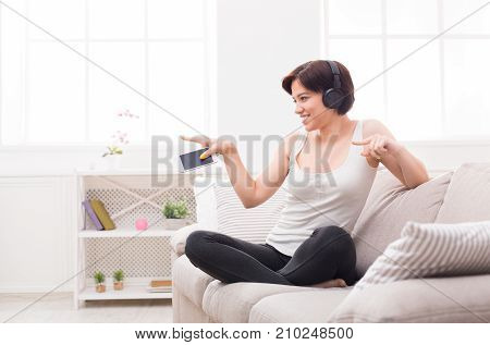 Move your body. Excited beautiful girl listening to music in headphones, holding her phone and pointing her fingers. Girl wearing casual clothes, sitting on cozy beige couch. Technology and enjoyment