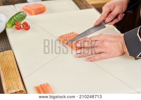 Chef slicing raw fresh salmon fillet. Chef hands with knife cutting salmon on white cutting board. Sushi cooking at professional kitchen.
