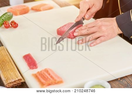 Chef cutting raw tuna on cutting board. Cook hands with knife slicing fresh fillet of tuna for making sushi. Chef at work, kitchen.