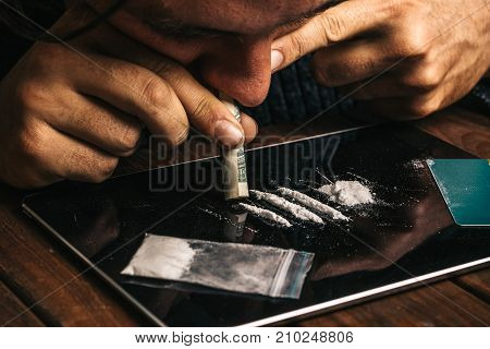 Drug addict man using or sniffing cocaine by nose with rolled dollar from tablet, Drugs Abuse concept