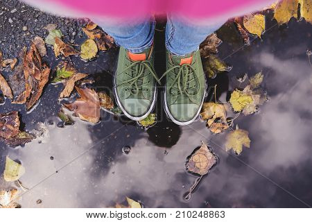 Selfie legs close-up in blue jeans and green sneakers standing in a puddle with yellow leaves in autumn in the park