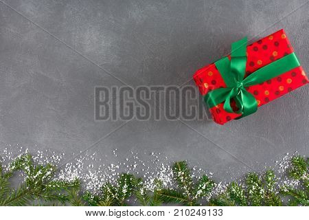 Handmade presents box in red dotted paper, fir, decorated snow. Xmas, new year concept. Top view, copy space, gray background