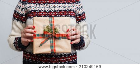 Unrecognizable woman holding christmas gift. Cropped image of girl in sweater with present box in hands, gray background. Preparing for xmas and new year, copy space