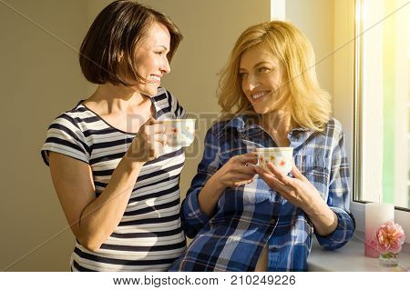 Beautiful adult woman holding hot cups of coffee drinking standing near the window and looking at each other sharing funny things enjoying sisters talking time