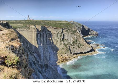 Espichel Cape lighthouse building over rocky cliffs Sesimbra Portugal