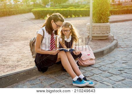 Schoolchildren reading a book sitting on the sidewalk. Urban background.