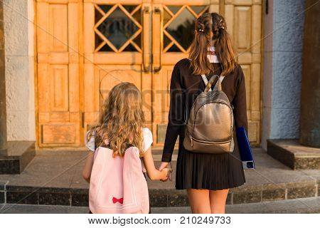 Outdoor portrait of two girls. A high school student and elementary school student holding hands go to school. Back view.
