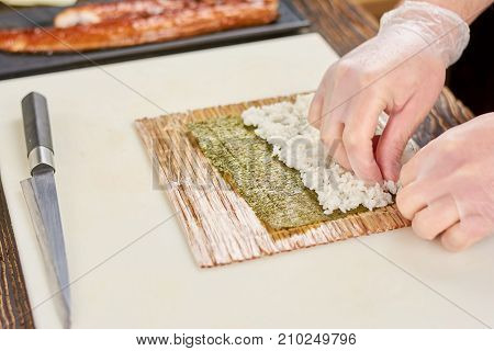 Male cook preparing sushi at restaurant. Chef hands cooking sushi with rice and nori. Process of japanese sushi roll preparation.