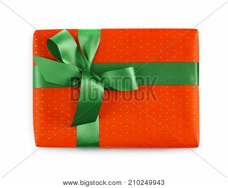 Gift box wrapped in red paper and green satin ribbon, isolated on white background. Modern present for any holiday, christmas, valentine or birthday