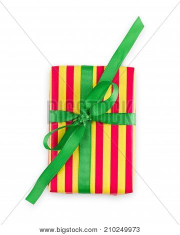 Gift box wrapped in striped red and yellow paper and green satin ribbon, isolated on white background. Modern present for any holiday, christmas, valentine or birthday