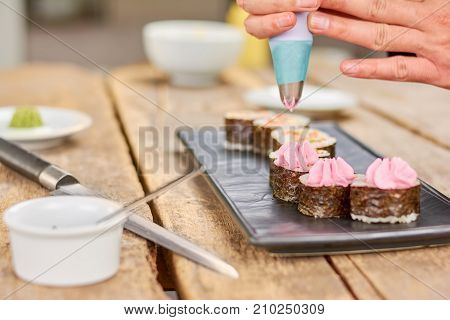 Chef preparing japanese sushi roll. Cook putting delicious cream on sushi with nori. Preparation of japanese traditional food.