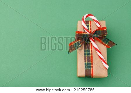 Handmade christmas gift box in craft paper with checkered ribbon on green background with copy space. Xmas, birthday, new year or valentine day present concept, top view