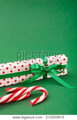 Handmade christmas gift box in dotted paper with green ribbon, xmas candies on green background with copy space, vertical. Xmas, birthday or valentine day present concept
