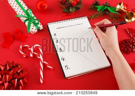 Preparing for christmas background. Female hand writting wish list. Open notebook with copy space, lollipops, gift box and small decorations on red surface