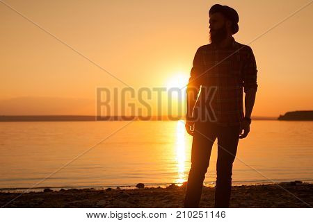 Silhouette of hipster man in hat posing on lake side in bright back light of sunset.
