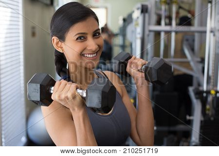 Closeup portrait young attractive woman lifting weight in gym indoors with equipment in the background