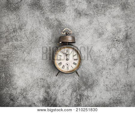 Vintage alarm clock on dark stone background. Five to twelve
