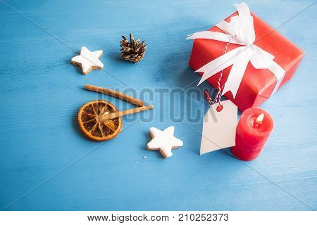 Gift wrapped in red paper and tied with white ribbon and bow with a blank tag attached to it surrounded by cinnamon sticks dried orange and star shaped cookies.