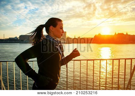 Silhouette of a beautiful young woman running in the sunset by the river in the city.