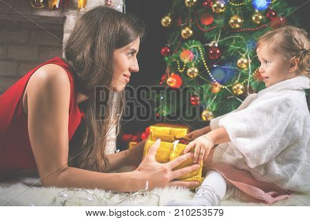 Cute baby and mum decorating a Christmas tree. Red balls. New Year 2018. Fairy tale. Mothercare is most important in children life. Baby and daughter