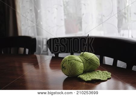 Clumps of yarn and knitting needles on the table in the room