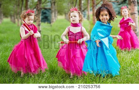 Collage with four little girls (two models) dressed in bright puffy gown examines standing on grassy lawn in park
