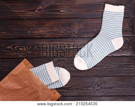Pair of women's striped socks whith a paper bag on a wooden background. Women's socks as a gift