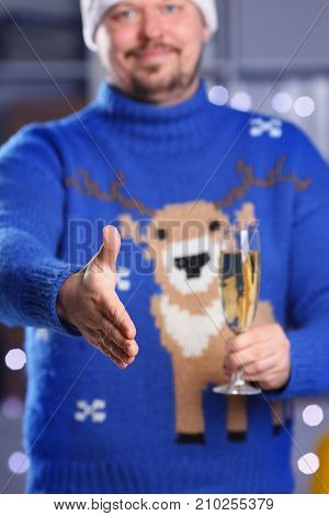 Man wearing warm blue deer sweater hold in arm champagne goblet give arm as hello in office with glowing garland in background closeup. Positive friend welcome strike bargain approval mediation offer