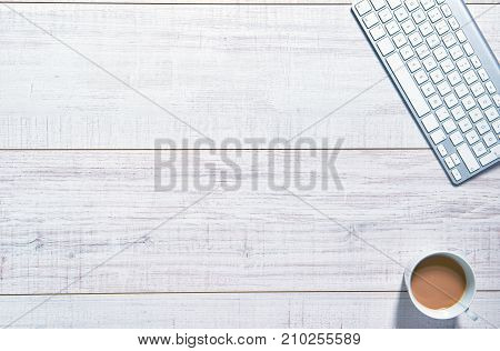 View of a wooden table with a keyboard and a cup of coffee on the side of it