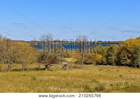 An isolated homemade deer stand  sets among a grove of autumn colored trees near a lake