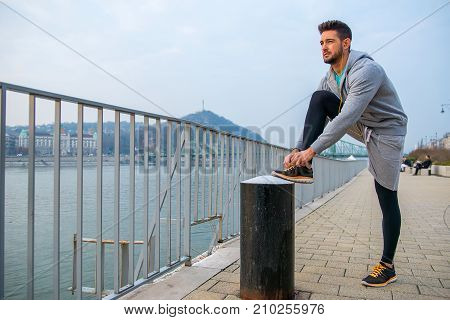 A handsome young sportsman ties his shoelace on the riverside
