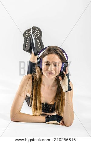 Dark hair girl, wearing a black top and leggins, is listening to music while lying on floor in headphones in the white isolated background