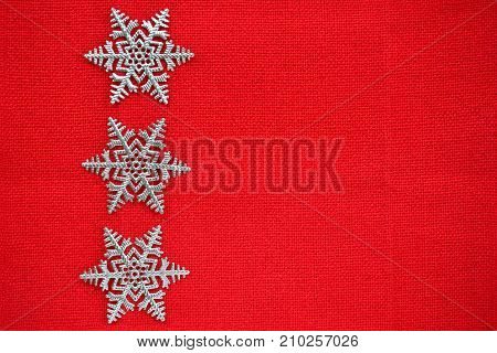 Silver snowflakes on textured red background in horizontal format with room for text