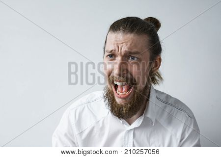Studio shot of outraged furious young man with thick beard and hair knot screaming with anger and rage frowning and opening mouth widely while having argument dispute or fight loosing his temper