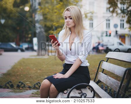 Girl using mobile phone - Smartphone in th city. Young beautiful blonde businesswoman surfing on her cellphone. Woman wearing white shirt.