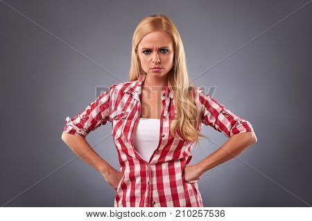 A beautiful young woman standing in a plaid shirt and feeling angry