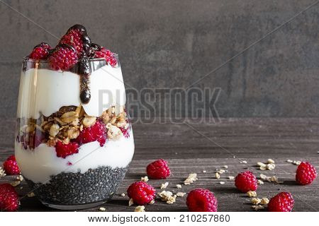 raspberry yogurt parfait in a glass with chocolate granola and chia seeds for healthy breakfast on rustic wooden background