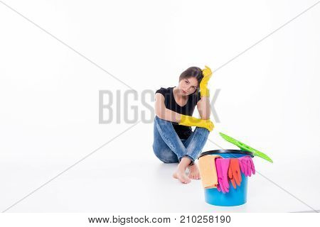 Young attractive woman tired of cleaning and housework isolated on white background.