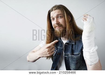 Upset bearded man posing at studio wall background with broken arm in bandage and gypsum. Unhappy guy pointing finger at white plaster covering his wrist arm and elbow. Trauma injury or fracture