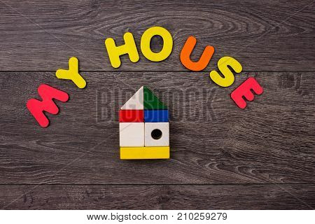 Word House from wooden letters on wooden background