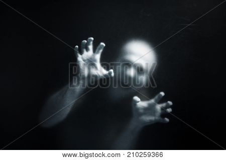 Screaming man behind a dusty scratched glass
