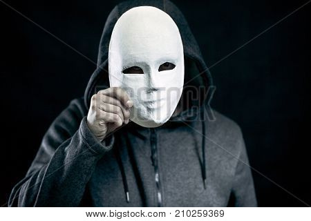 Man holding white mask for hide his face
