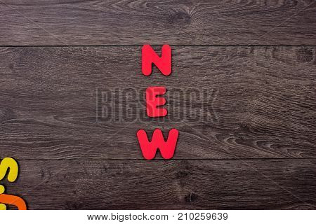 Word New from wooden letters on wooden background