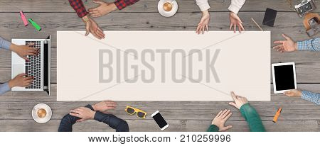 Business Teamwork concept - top view of six casual business people. White blank sheet of paper in the middle of the wooden table.