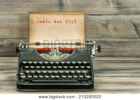 Antique typewriter with grungy paper on wooden background. Goals for 2018. Business concept. Selective focus