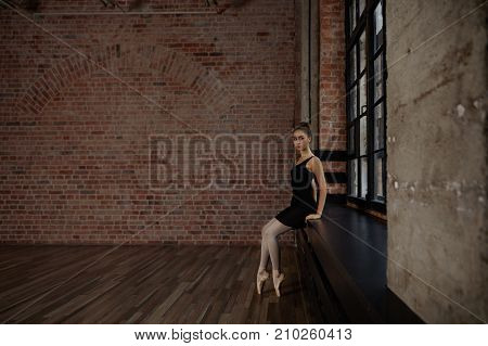 Portrait of elegant slim young Russian ballerina in black pack white pantyhose and ballet shoes sitting on wide windowsill in studio and relaxing during intense exercise preparing for performance