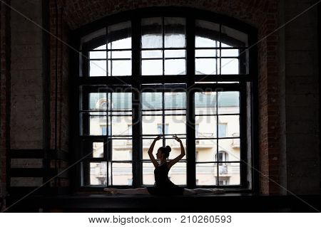 Silhouette of attractive slim flexible young European female ballet dancer girl wearing black tutu and pointe shoes raising her slender arms while stretching at large window doing right split